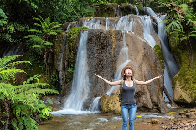 Girl traveling at waterfall. tourism day.