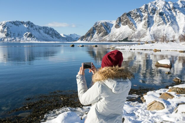 Girl travels around lofoten islands and takes pictures on camera. beautiful norwegian landscape. norway