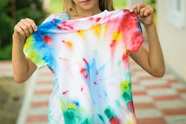 The girl tries on a t-shirt painted in the style of tie dye.