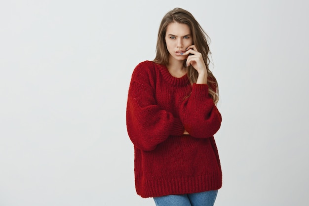 Girl trying to concentrate on math lesson. portrait of beautiful feminine woman in red loose sweater squinting while looking focused , holding hand on face, making calculations in mind