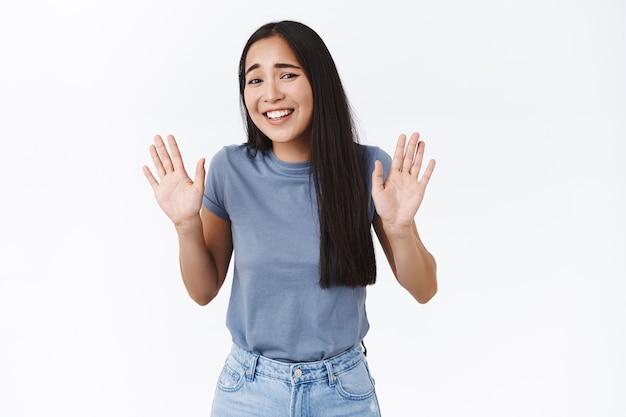 Девушка пытается в шутку отказаться от странного предложения, отступает и неловко смеется, поднимает руки в знак капитуляции или отказа, глупо улыбается, извиняется за то, что не пришла на вечеринку, стоит у белой стены