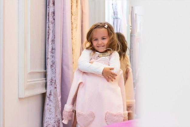Девушка примеряет одежду в примерочной в магазине одежды.
