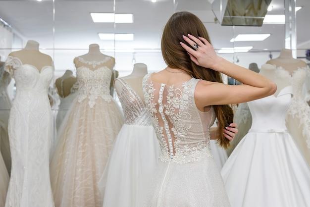 Девушка примеряет свадебное платье в салоне, стоя назад