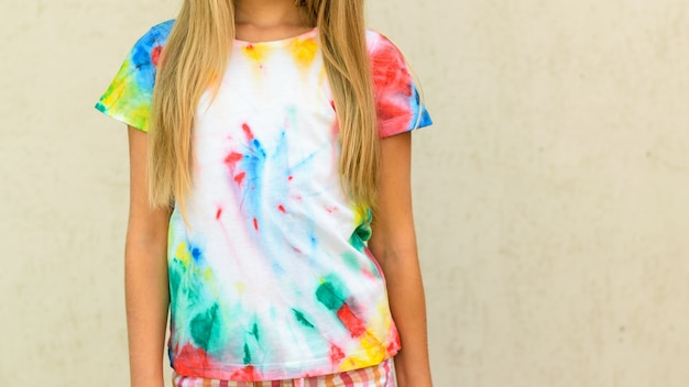 Girl trying on a t-shirt painted in the style of tie dye.