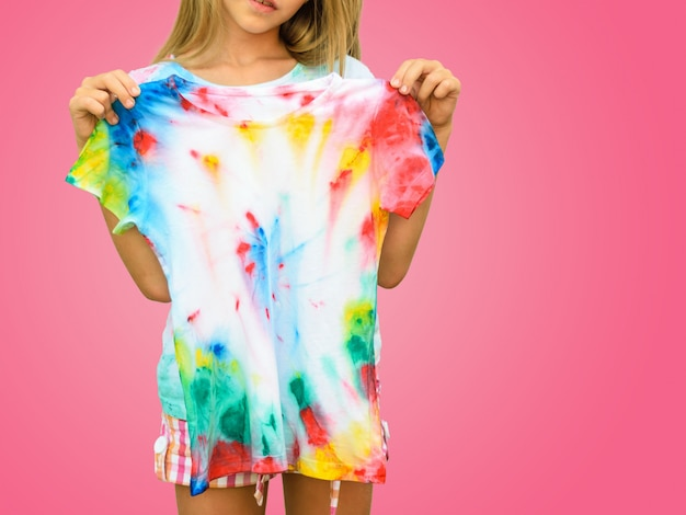 Girl trying on a t-shirt in the style of tie dye on a red wall.