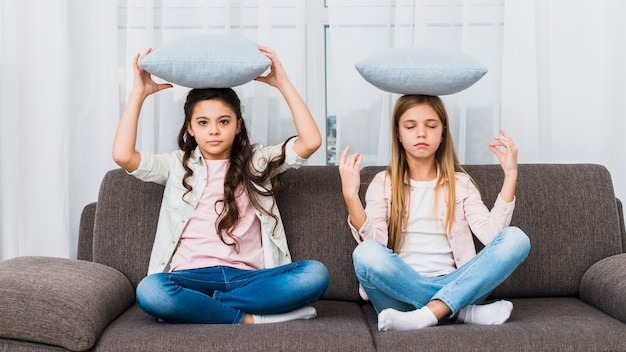 Girl trying to do yoga like her friend mediating on sofa with cushion