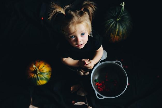 Девочка, заправленные в миску с тыквами вокруг глядя выше