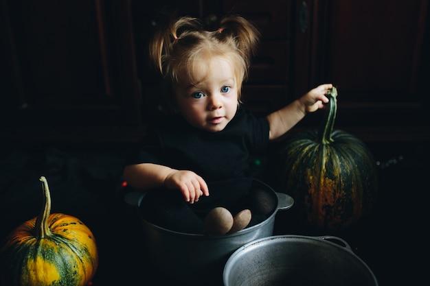 Девочка, заправленные в миску с тыквами вокруг