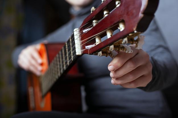 女の子はアコースティックギターのクローズアップを調整します。楽器を演奏します。