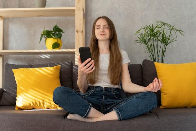 Девушка включила заклинание на телефоне и медитирует. женщина сидит в позе лотоса и включает медитацию на своем смартфоне.