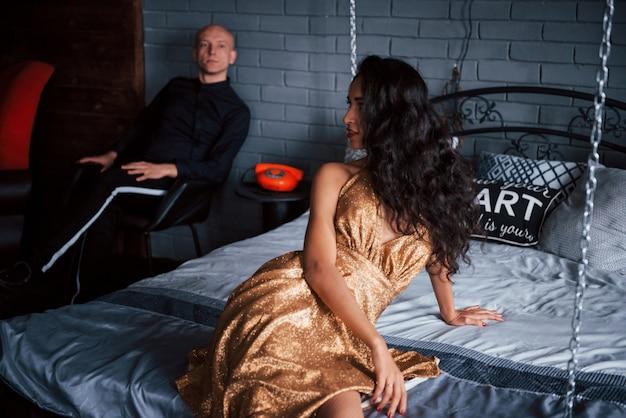 Девушка повернулась, чтобы посмотреть на мужа. пара в классической одежде сидит перед красивой роскошно украшенной кроватью
