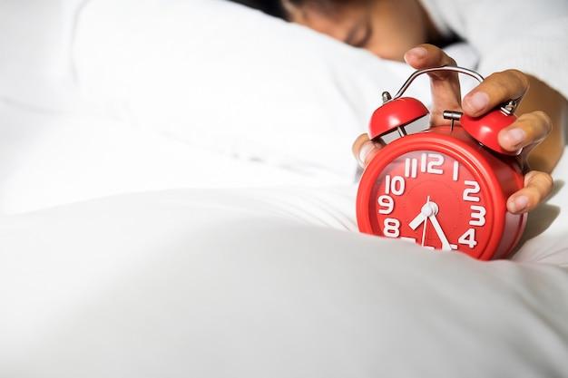 Девушка выключает будильник, просыпаясь утром от звонка