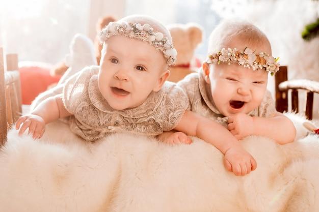 Девочки-близнецы в венках и платьях лежат на кровати в лучах утреннего солнца