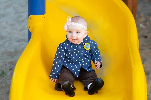 公園の遊び場で黄色の丘に乗ってジャケットの女の子2歳ブルネット