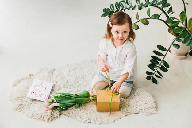 Girl tying bow on gift box near greeting card
