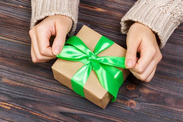 Girl tying bow on gift box