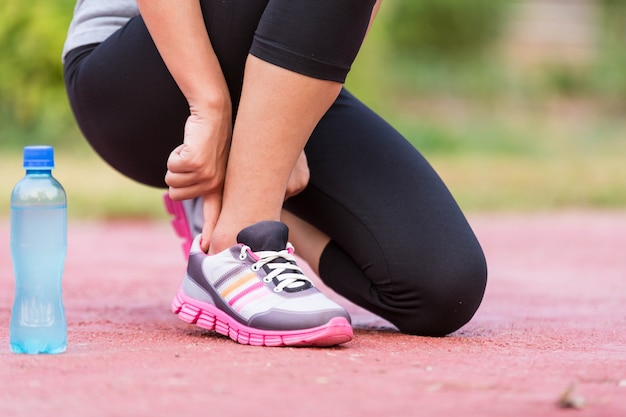 Girl tying jogging shoes. a person running outdoors on a sunny day