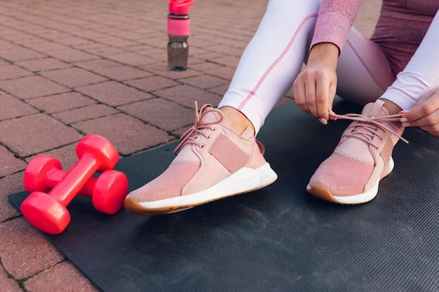 スニーカーで靴ひもを結ぶ女の子