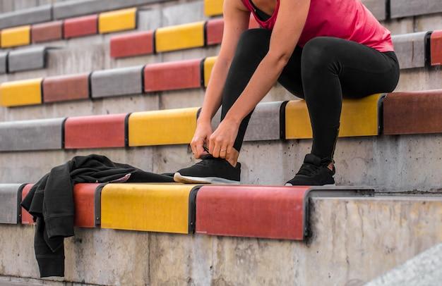 Девушка завязывает шнурки на кроссовках