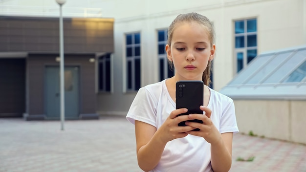 Girl types on smartphone. young blonde teenage girl with ponytail looks at display and swipes social nets standing on city pavement, copyspace