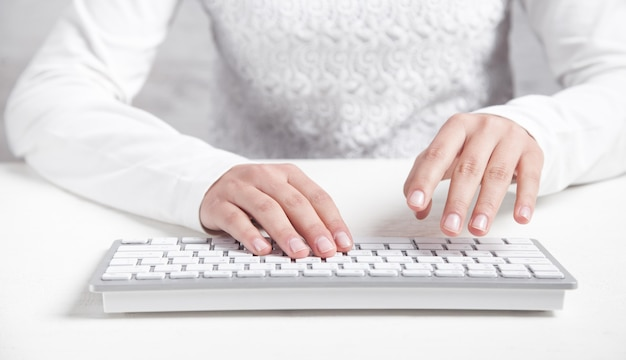 Girl typing on computer keyboard in office desk.