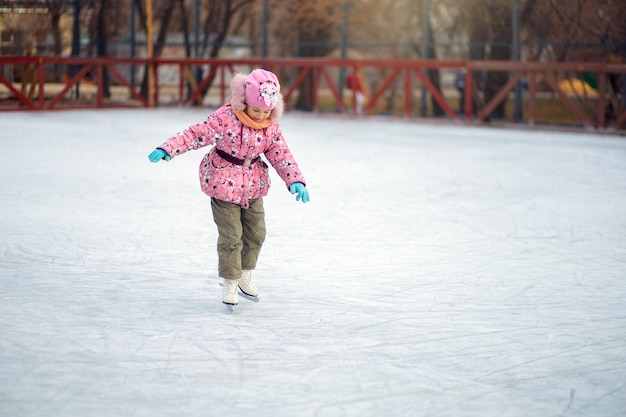 Girl uncertainly stands on figure skates on an ice rink and tries to ride