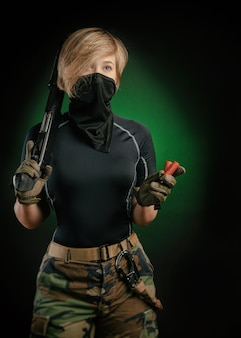 The girl in uniform with a gun posing, aiming, reloading, shooting, on a dark background in the studio