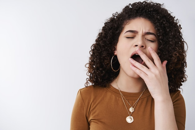 Girl uninterested falling asleep boring talks. cute 20s curly-haired female yawning closed eyes cover opened mouth palm feel sleepy tired boredom, need coffee get up early morning work