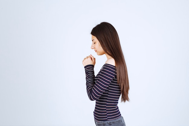 Girl uniting her hands and praying.