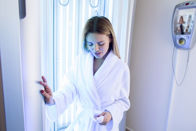 Girl unleashes a belt on a bathrobe standing in a solarium with neon light