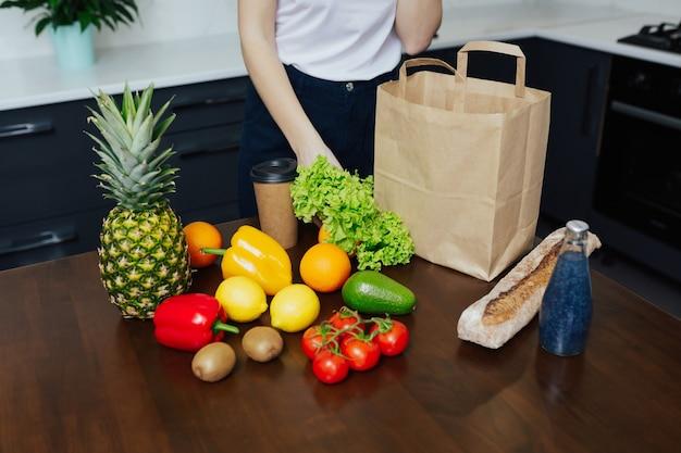 Девушка распаковывает бумажный пакет с фруктами и овощами на кухне после покупок.