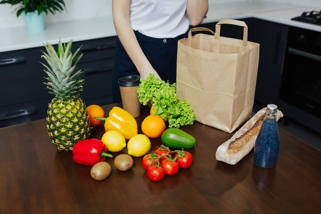Girl unpacking paper bag with fruits and vegetables in kitchen after shopping.