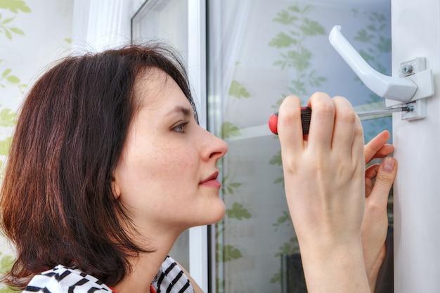 Girl unscrews fastening screws handle window using screwdriver.