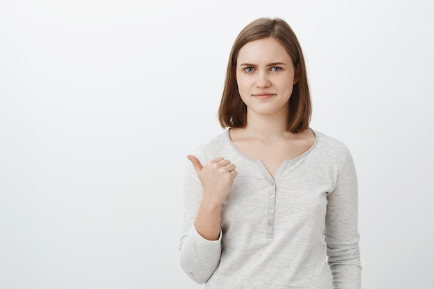 Girl unwilling bring lame classmate to party pointing backwards with thumb smirking displeased and dissatisfied rejection offer disapproving bad choice of friend standing unimpressed against grey wall