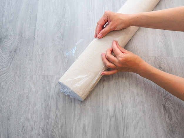 Girl unwrapping wallpaper on the floor