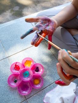 女の子は指に水彩画を描くためにブラシを使用します