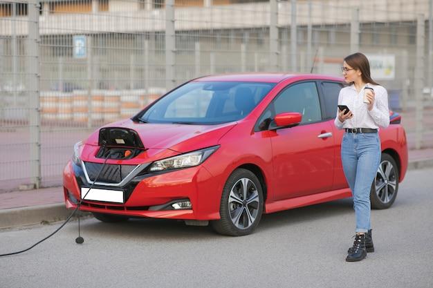 車でバッテリーを充電するためにスマートフォンを使用して電源を待っている間に女の子がコーヒーを飲む