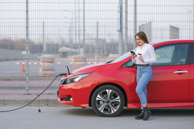 Girl use coffee drink while using smart phone and waiting power supply connect to electric vehicles for charging the battery in car.