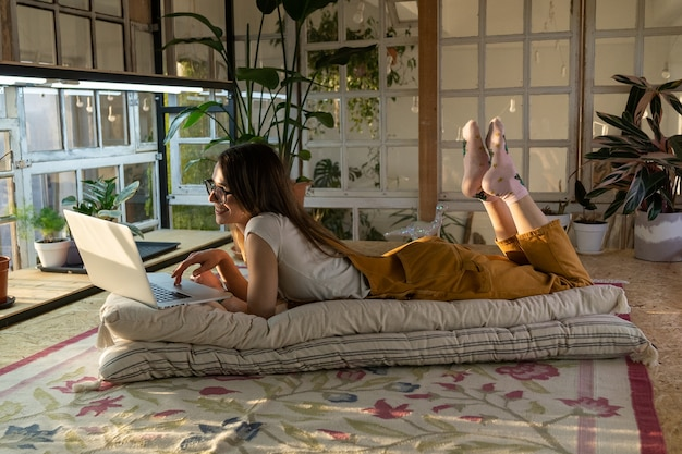 Girl use laptop lying on floor in room with retro furniture and plants florist relax after work