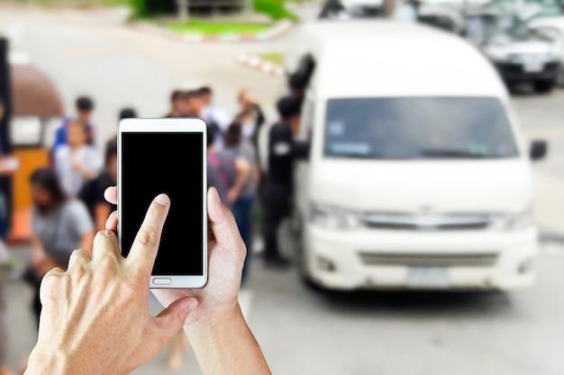 Девушка использует мобильный телефон, размытие изображения фургонов и туристов в качестве фона.