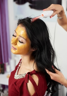 Girl uses darsonval for massage head's skin, with gold mask on face in a beauty salon. close-up