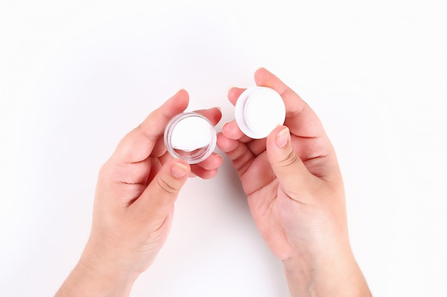 Girl uses hand cream on white. top view.