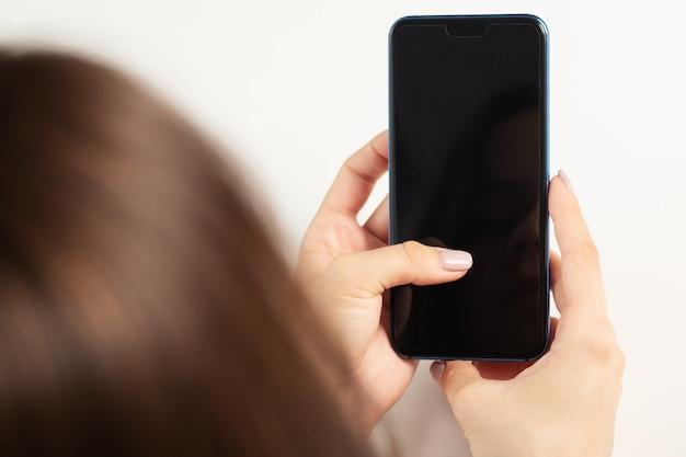 소녀는 전화 타이핑 sms를 사용하고 소셜 미디어, 모바일 앱을 봅니다.
