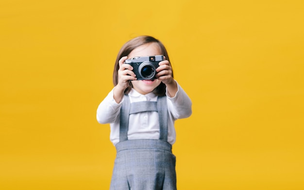 Девушка с помощью фотоаппарата на желтой стене