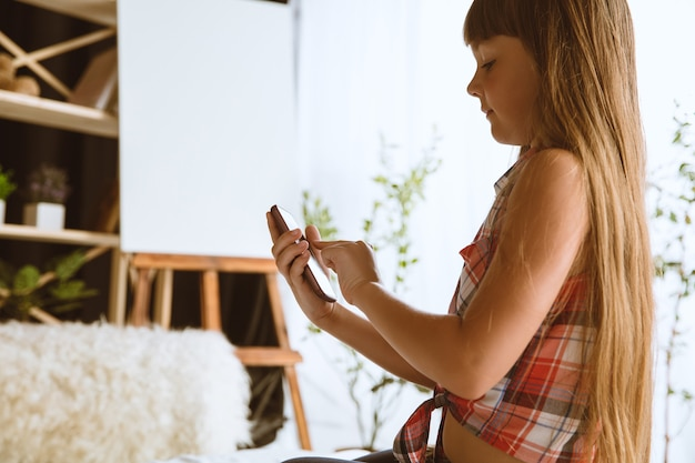 Девушка дома с помощью различных устройств. маленькая модель сидит в постели со смартфоном и делает селфи или использует видеочат со своими друзьями. концепция взаимодействия детей и современных технологий.