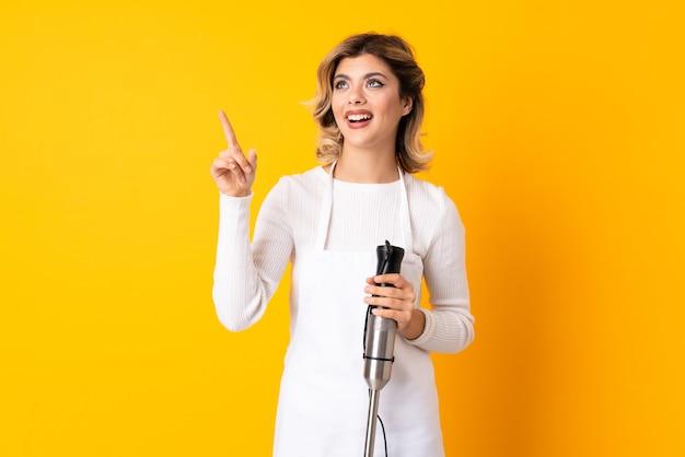 Девушка с помощью ручного блендера изолирована на желтой стене, указывая в сторону