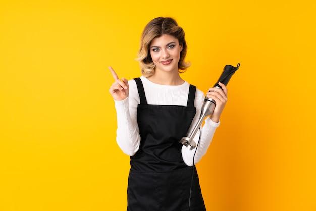 노란색 벽에 고립 된 핸드 블렌더를 사용하는 소녀와 최고의 기호에 손가락을 들어 올려