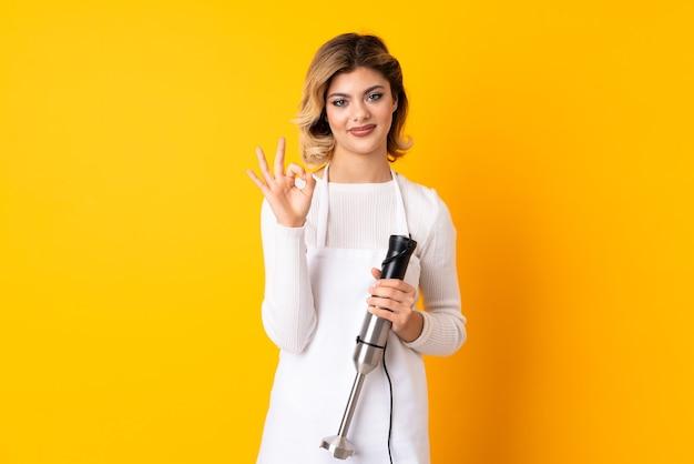 指でokサインを示す黄色の壁に分離されたハンドブレンダーを使用して女の子