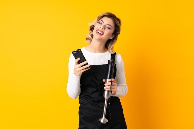 승리 위치에서 전화와 노란색에 고립 된 핸드 블렌더를 사용하는 소녀