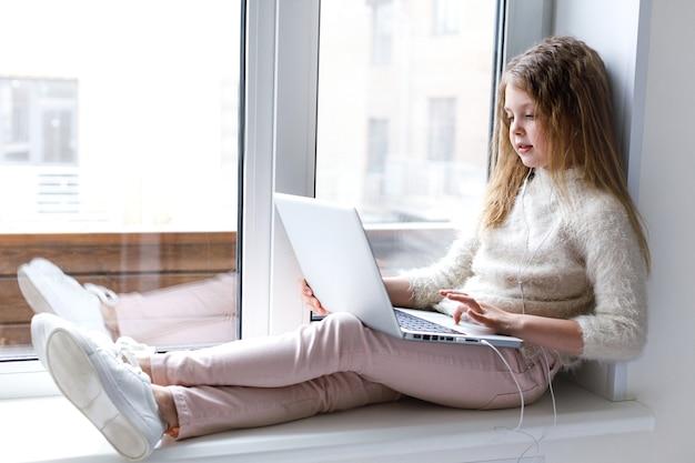 オンライン教育と遠隔学習のために自宅でノートパソコンを使う女の子